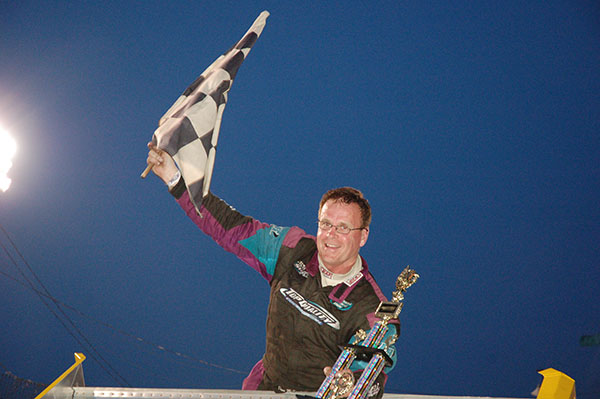 Dave McKnight stands on supermodified after Anderson Speedway win.