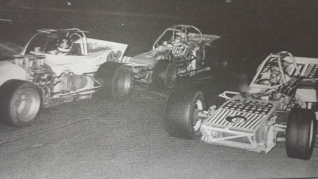 Jim Shampine passes Bobby Stelter at 1974 Oswego Speedway International Classic by Speedway Press